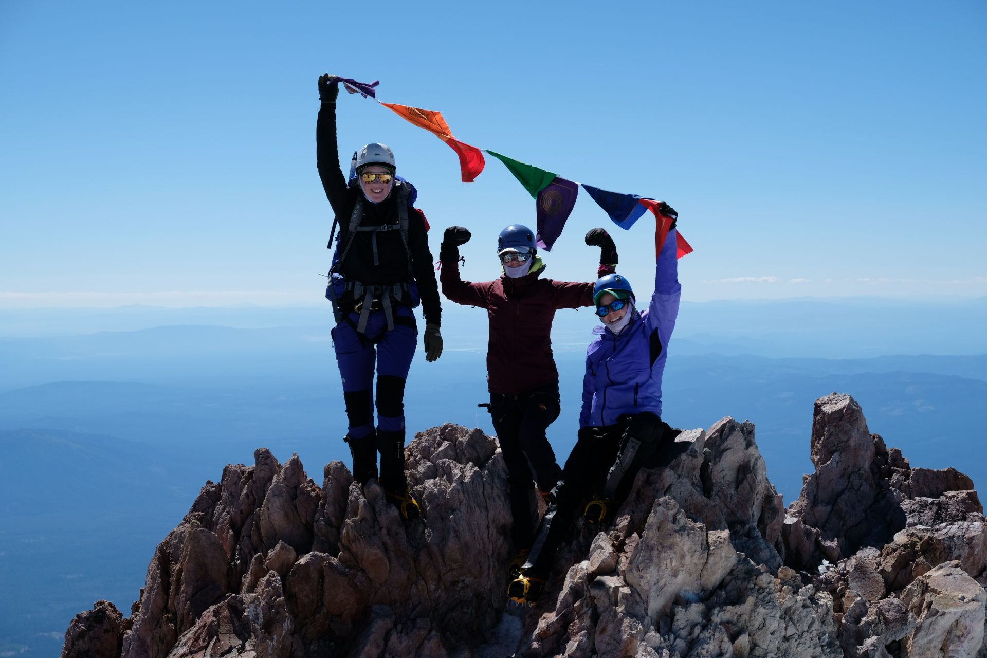 At the top of Mount Shasta, Climb Against the Odds climbers fly prayer flags in honor and memory of those affected by breast cancer and other diseases