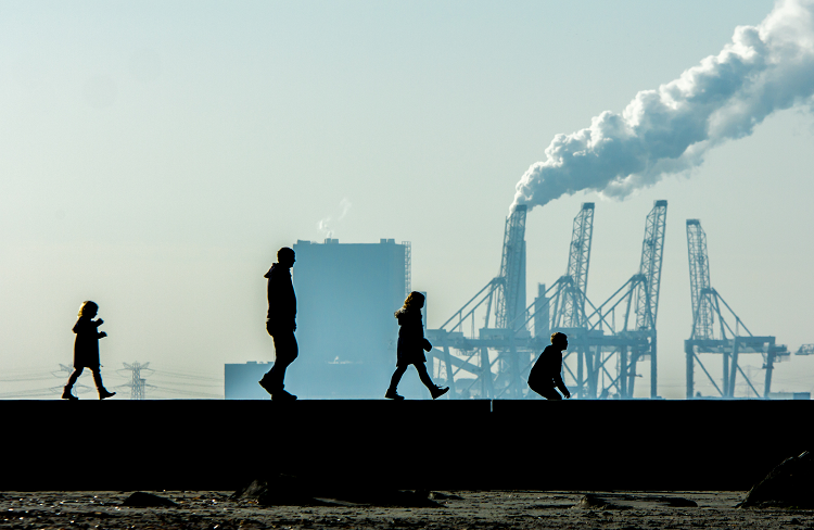 family-walking-in-front-of-smoke-stacks_istock_BCPP